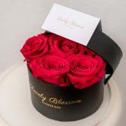 Crna okrugla kutija sa crvenim ružama