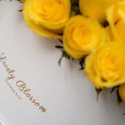 Žute ruže u bijeloj okrugloj kutiji