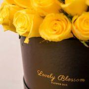 Žute ruže u crnoj okrugloj kutiji