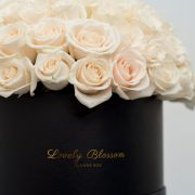 Bijele ruže u crnoj okrugloj kutiji