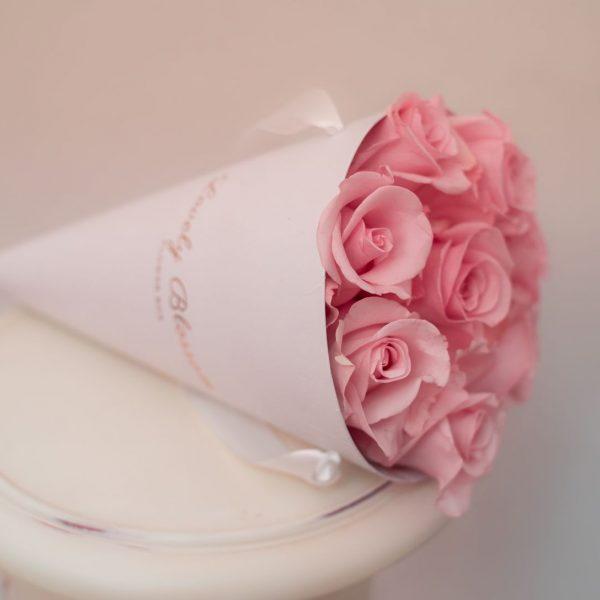 Roze ruže u bijeloj stozac kutiji